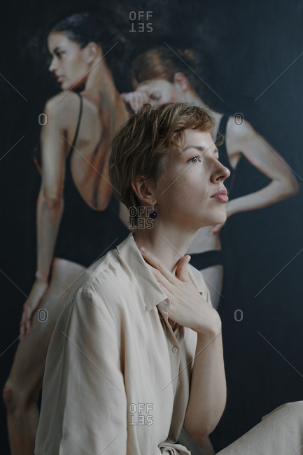 Thoughtful mid adult female artist looking away with hand on neck while sitting by painting