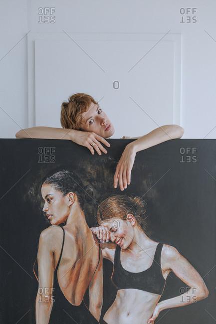 Mid adult female artist standing behind painting in studio