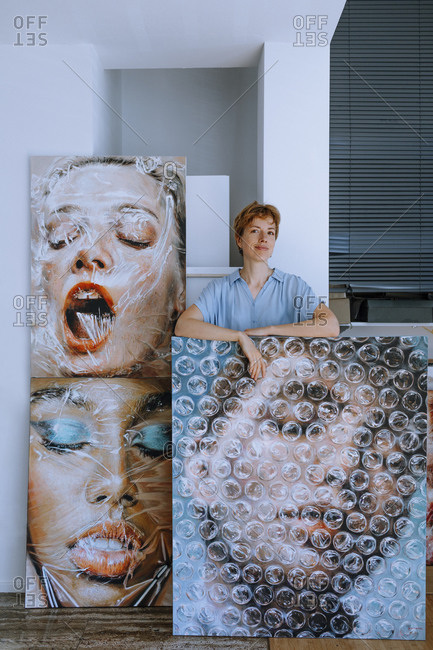 Smiling female artist standing with paintings in art studio