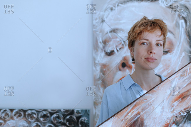 Confident mid adult female artist with paintings against wall in art studio