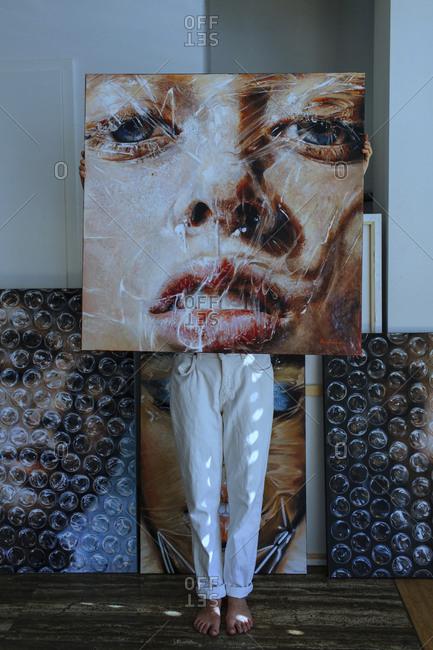 Female artist standing behind painting against wall in art studio