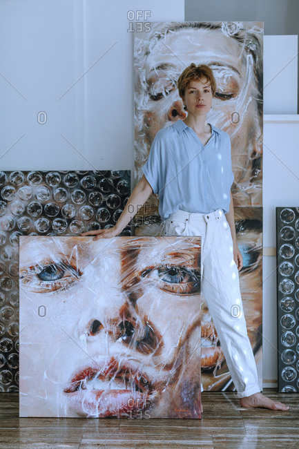 Confident mid adult female artist standing with various paintings in art studio