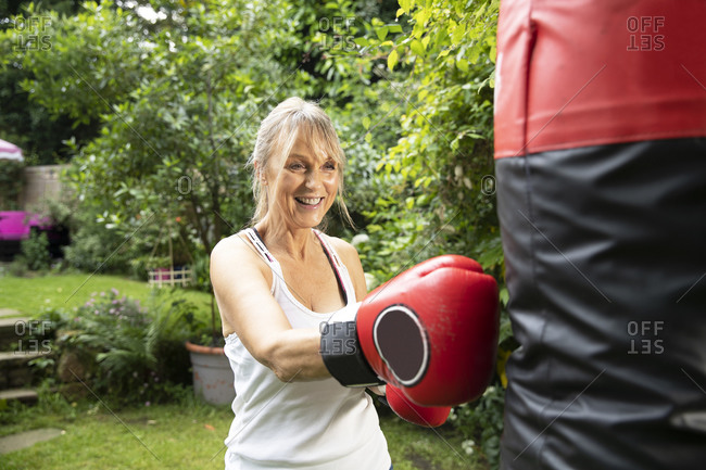 Active senior woman punching punch bag while standing in back yard on sunny day