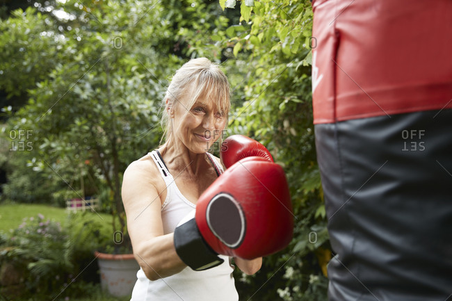 Senior woman punching punch bag while standing in back yard on sunny day