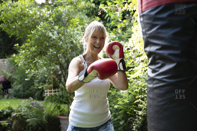 Cheerful senior woman punching punch bag while standing in back yard on sunny day
