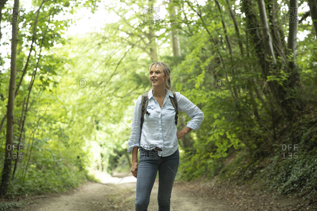 Senior woman with hand on hip looking away while exploring in forest