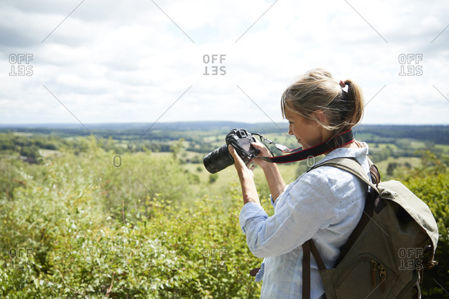 Active senior woman taking picture with camera of scenic view on sunny day