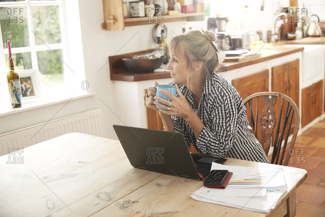 Senior holding coffee cup looking away while sitting with laptop on table in kitchen at home