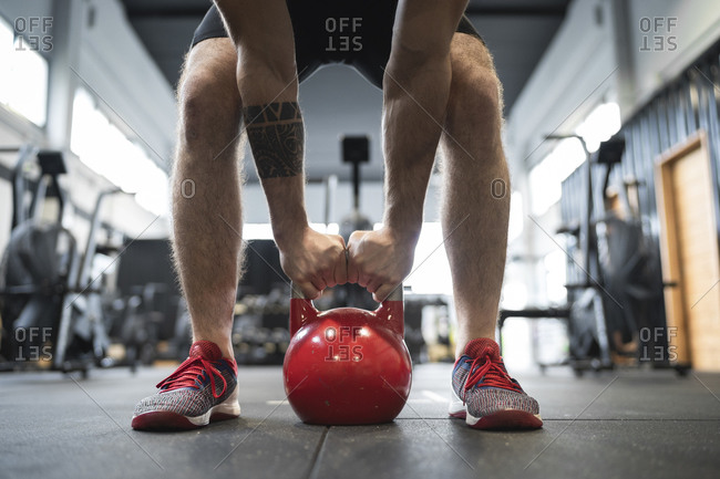 Legs of male athlete holding kettlebell while standing in gym