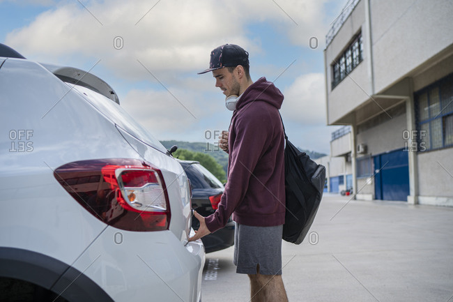 Mid adult man opening car trunk while standing at parking lot