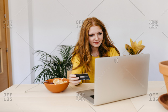 Young woman using credit card while doing online payment sitting at home