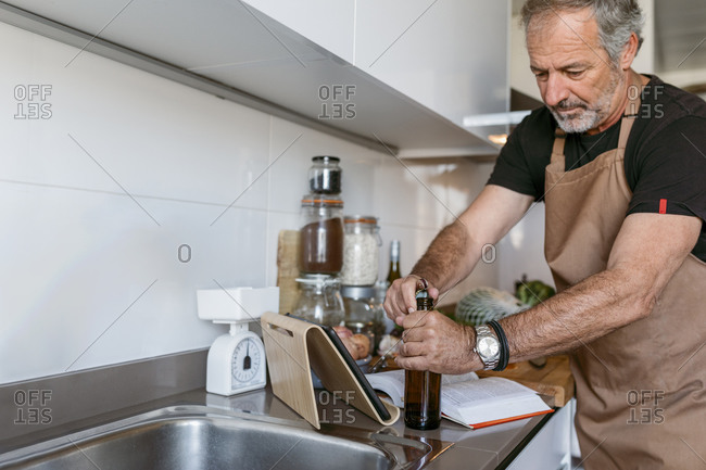 Mature man opening beer bottle while standing in kitchen