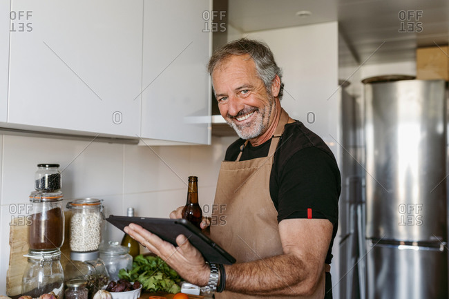 Smiling man holding beer bottle and digital tablet while standing in kitchen at home