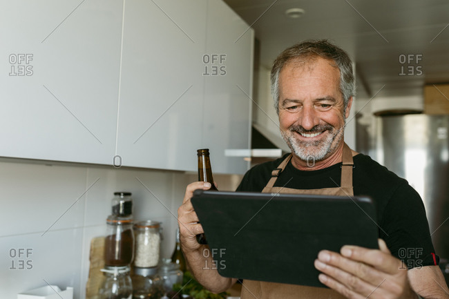 Smiling man holding beer bottle while using digital tablet standing in kitchen at home