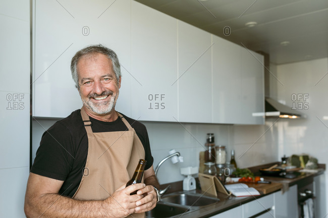 Smiling man holding beer bottle while standing in kitchen at home