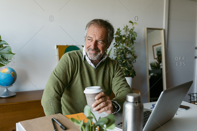 Mature man looking away while holding disposable coffee cup while sitting at home