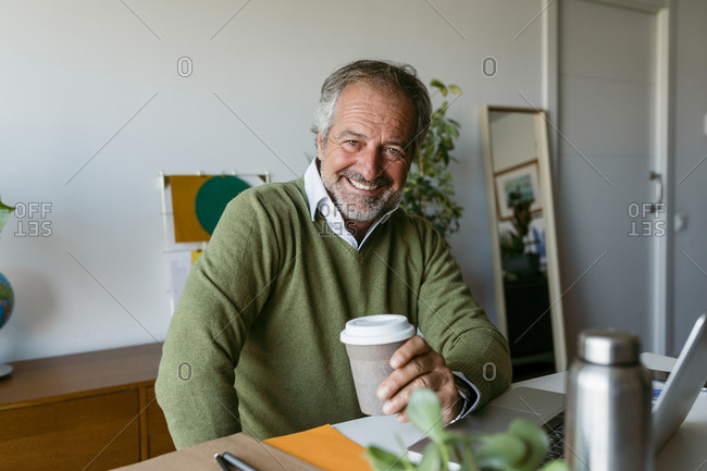 Smiling mature man holding disposable coffee cup sitting at home