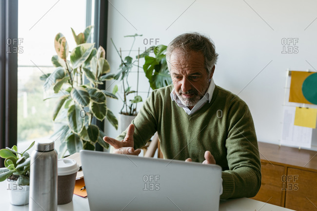 Mature man doing video call on laptop while sitting at home