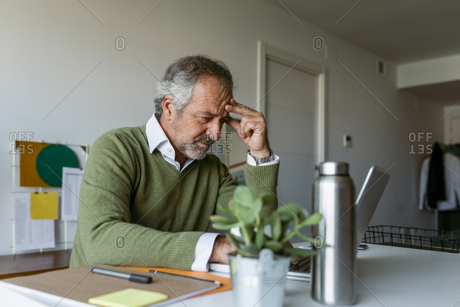Mature man worried while working on laptop at home