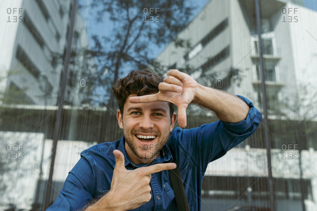 Cheerful businessman making finger frame against modern glass building
