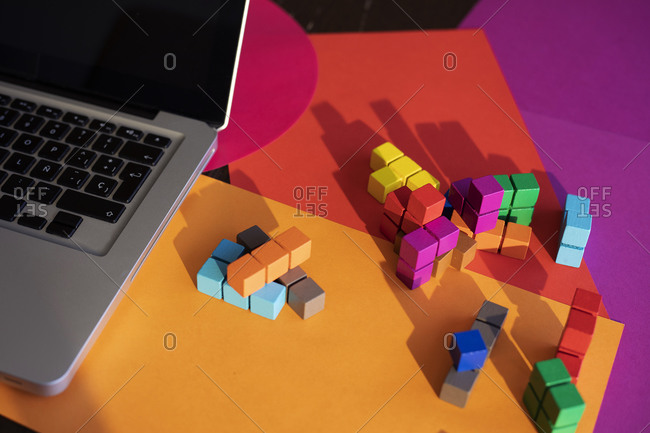 Laptop and colorful blocks on table at home
