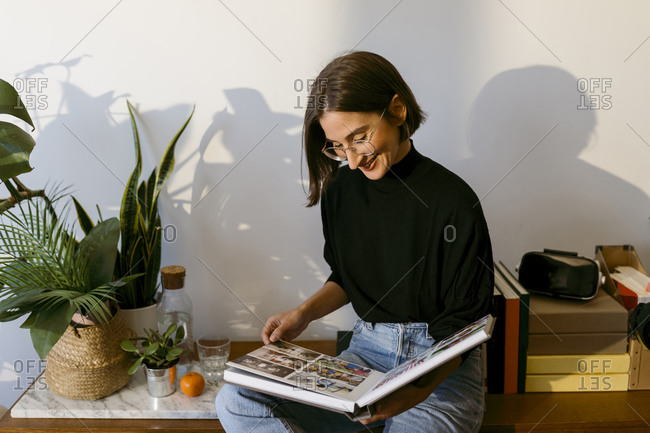 Smiling woman looking photographs in photo album while sitting at home
