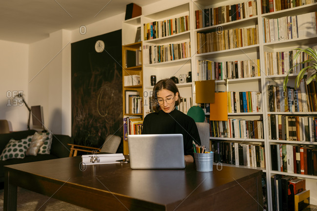 Female freelancer working on laptop sitting against bookshelf at home