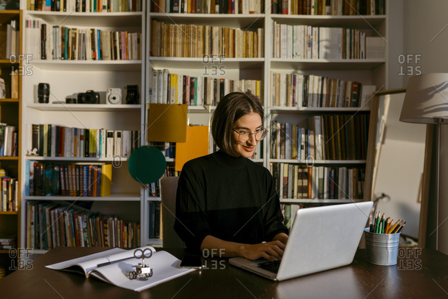 Smiling businesswoman working on laptop sitting against bookshelf at home