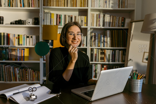 Businesswoman with hand on chin using laptop while sitting against bookshelf