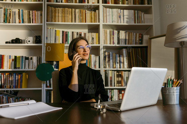 Businesswoman talking on smart phone looking away sitting by laptop against bookshelf at home