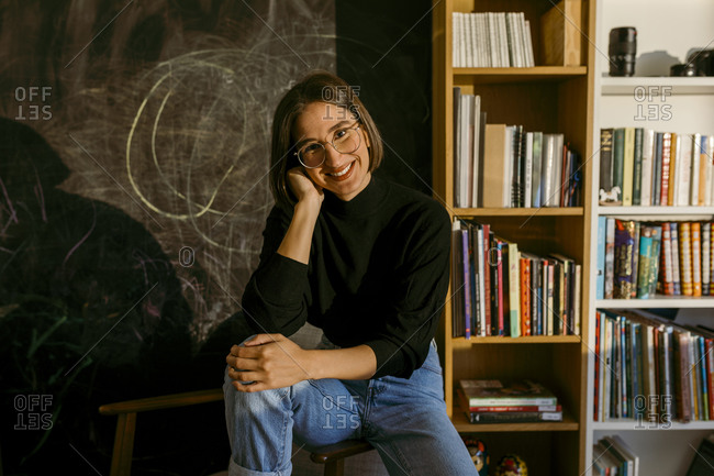 Smiling woman with hand in hair sitting against bookshelf at home