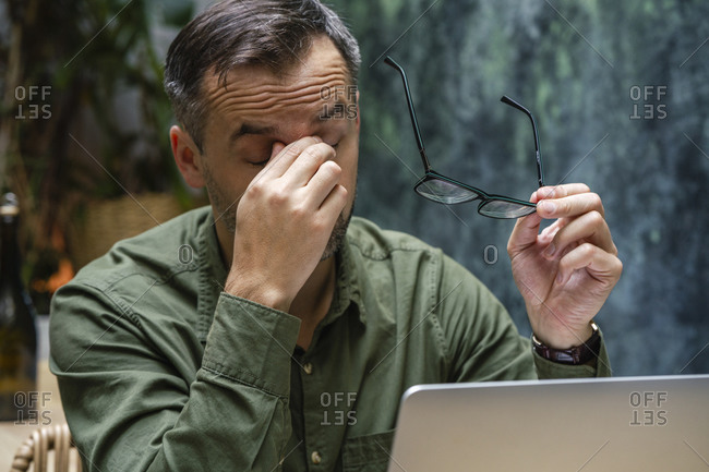 Tired businessman with head in hands working on laptop while sitting at cafe