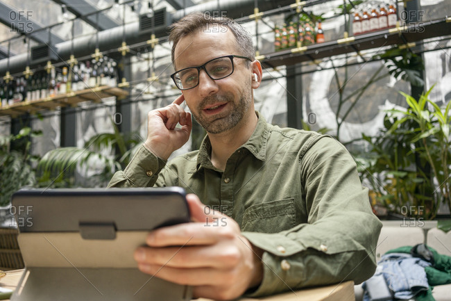 Businessman adjusting in-ear headphones while using digital tablet at cafe