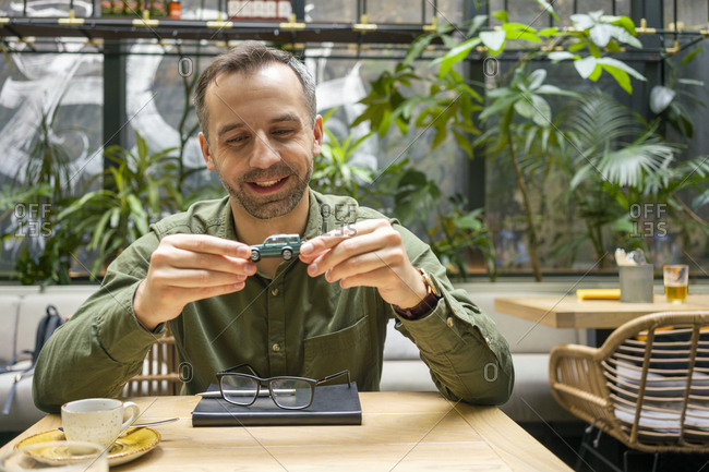 Smiling businessman holding toy car while sitting at cafe