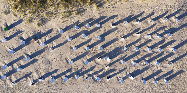Aerial view of rows of hooded beach chairs on sandy beach