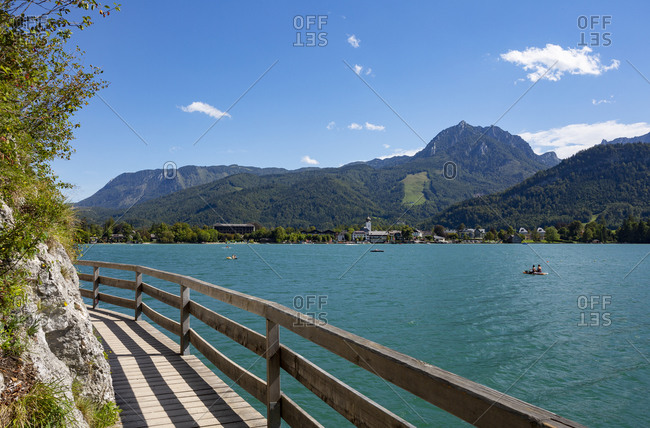 Austria- Salzburg- Strobl Am Wolfgangsee- Boardwalk stretching along shore of Lake Wolfgangsee in summer with forested mountains in background