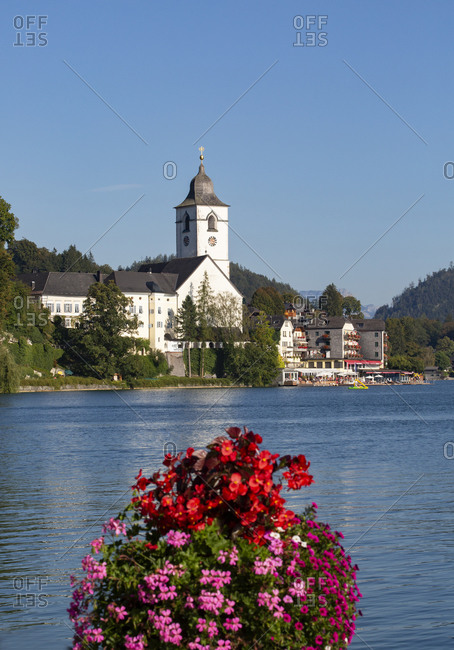 Austria- Upper Austria- Saint Wolfgang im Salzkammergut- Flowers blooming over shore of Lake Wolfgangsee in summer with church in background