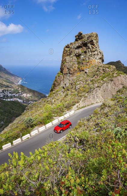 Red car driving along highway in Macizo de Anaga range