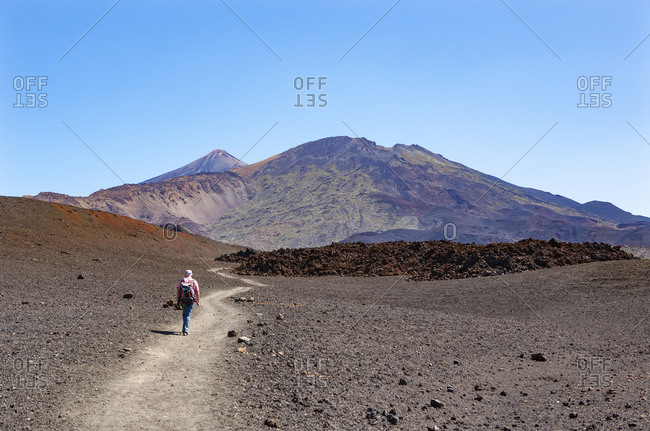 Senior man hiking along trail stretching across brown barren landscape of Tenerife island