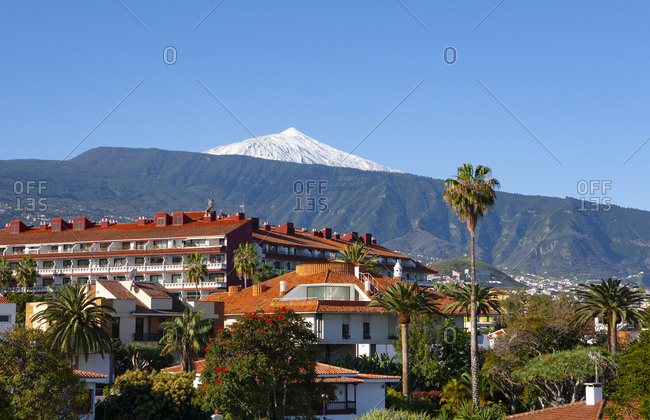 Spain- Province of Santa Cruz de Tenerife- Puerto de la Cruz- Buildings of coastal city in summer with Mount Teide looming in distant background