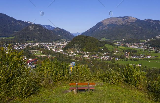 Empty bench amidst plants near town on sunny day- Salzkammergut- Austria