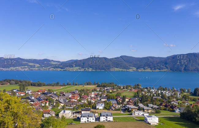 Drone view of town by lake and mountains against blue sky on sunny day- Attersee- Salzkammergut- Austria