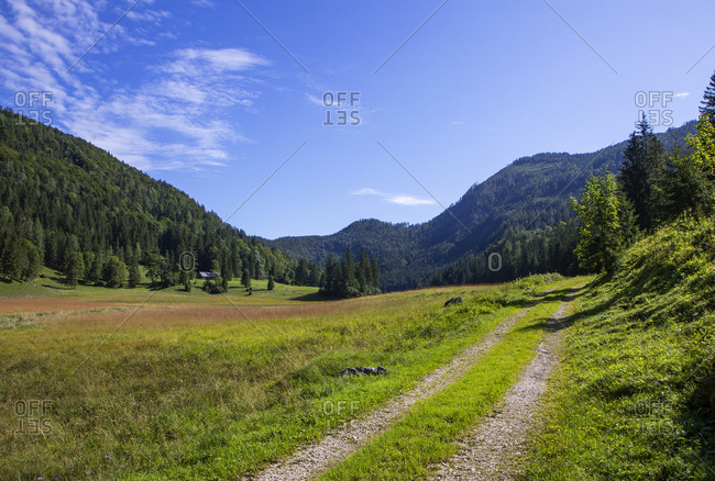 Pathway leading towards mountain against blue sky- Salzkammergut- Austria