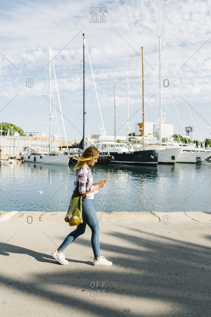 Young woman text messaging on smart phone while walking at seaside