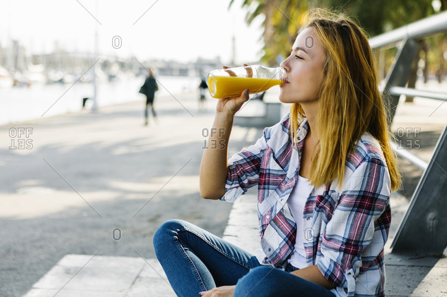 Young woman drinking juice while sitting on footpath in city