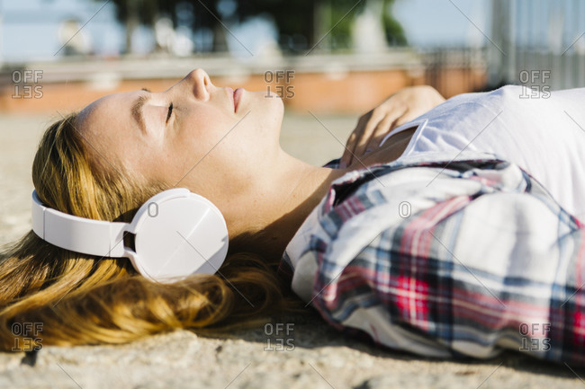 Woman lying on back listening music through headphone during sunny day