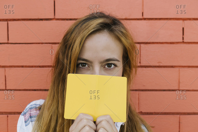 Young woman covering face with yellow paper against brick wall