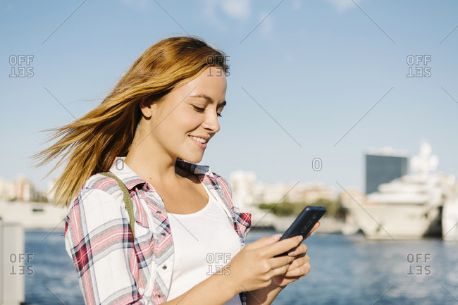Woman text messaging on smart phone while standing at seaside during sunny day