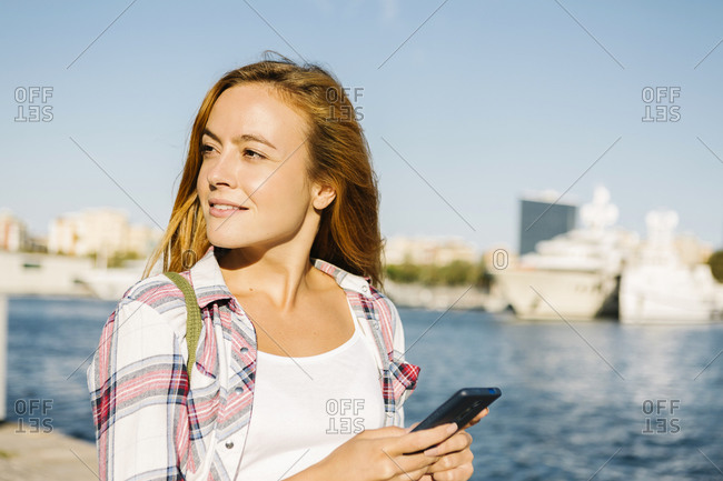 Woman using smart phone looking away while standing at seaside on sunny day