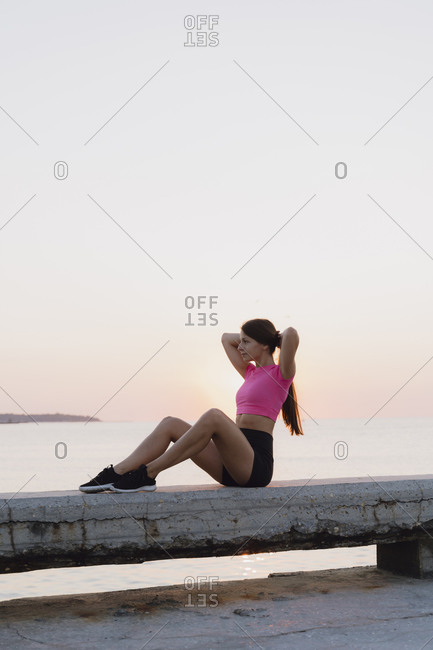 Athlete tying hair while sitting on concrete wall against sea